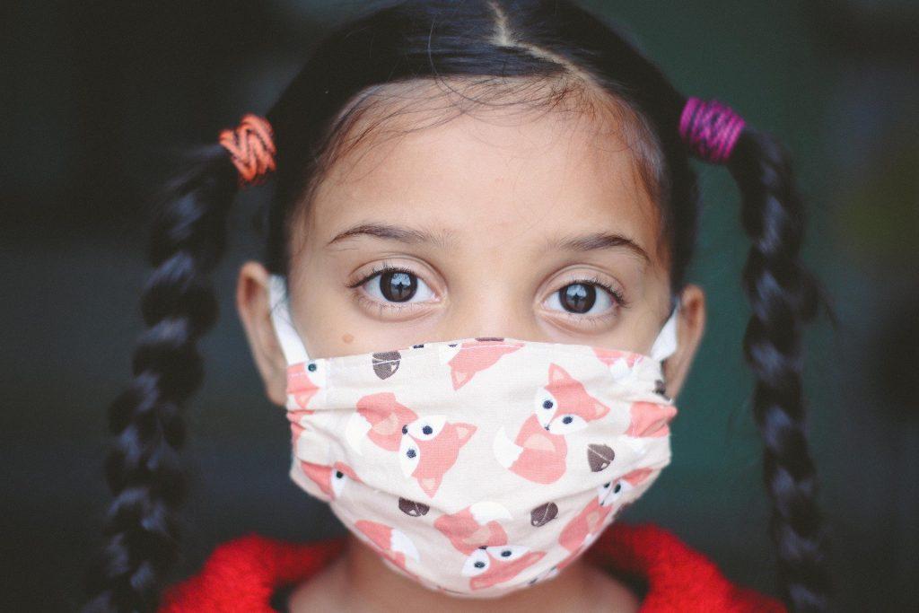 Kind trägt einen bunten Mundschutz
